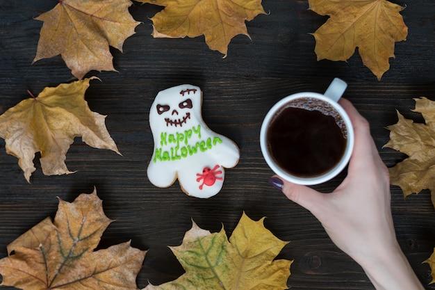 女性の手でコーヒーカップと言葉でジンジャーブレッドクッキーゴーストハッピーハロウィン