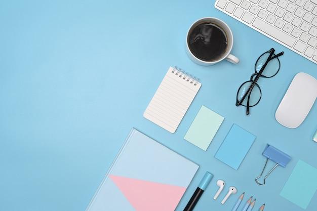 Чашка кофе, клавиатура, очки и канцелярские принадлежности на синем фоне.