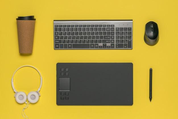 Чашка кофе, клавиатура, мышь и графический планшет на желтом