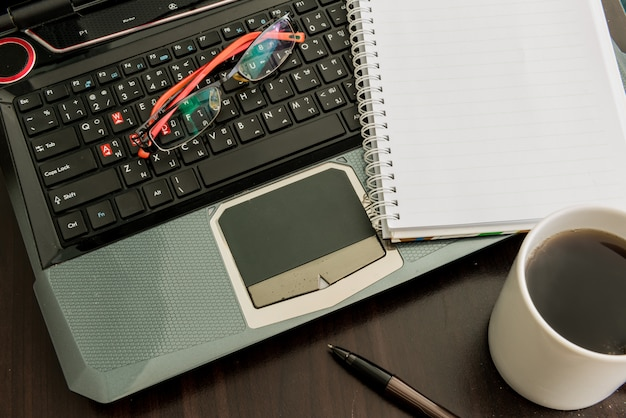 Coffee cup, laptop, pen , notepad and glasses on wooden table