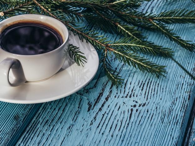 Coffee cup on light green fir tree.