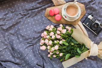 Coffee cup; macaroons; camera and flower bouquet on tablecloth