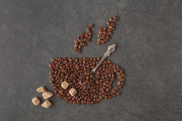Coffee cup made of beans on dark background