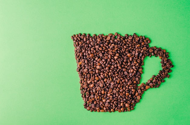 Coffee cup made of coffee beans on a green background - perfect for a cool wallpaper