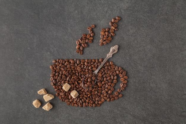 暗い背景に豆で作られたコーヒーカップ
