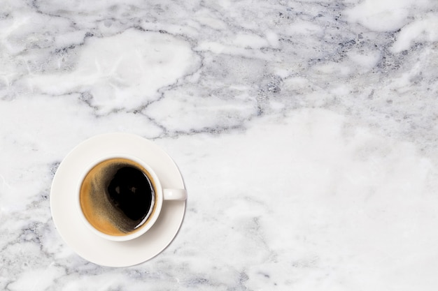 Coffee cup on marble table top view.