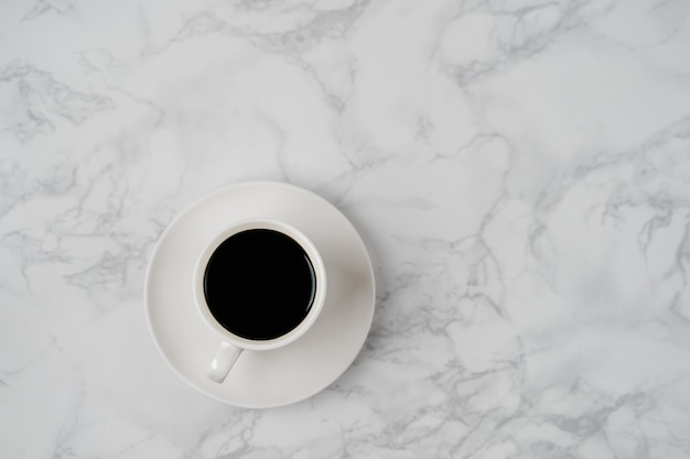 Coffee cup on marble texture table, black coffee cup in top view with copyspace