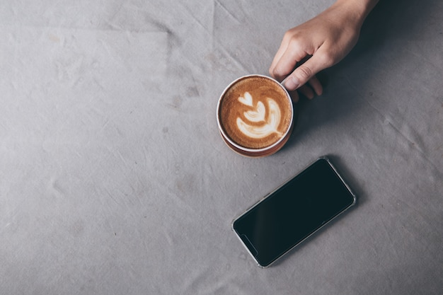 Coffee cup and mobile phone on gray tablecloth with stain background.