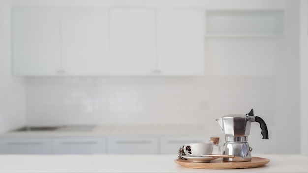 Coffee cup and moka pot in wooden tray on white counter with blurred kitchen background