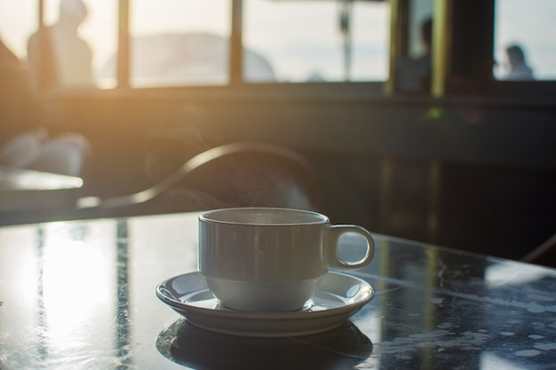 Coffee cup at morning with sunlight. soft focus.