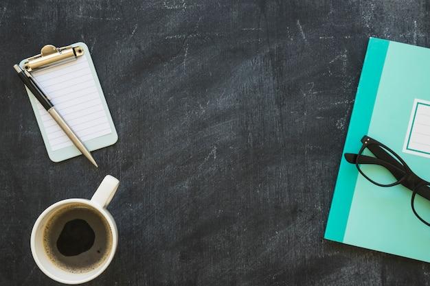 Coffee cup; notebook; eyeglasses; pen and notepad on blackboard