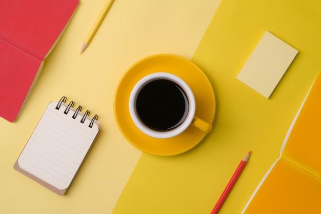Чашка кофе, тетради и карандаши на желтом фоне.
