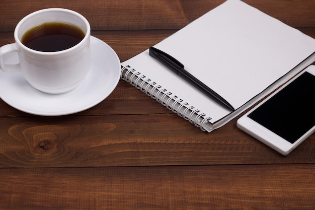 Coffee cup, notepad, pen, cell phone wooden background