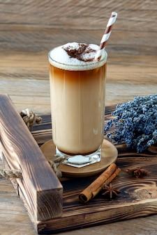 木製のトレイに自家製ラベンダーシロップと花とラテのコーヒーカップ。居心地の良い朝食。