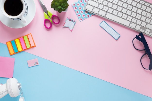Coffee cup; office stationeries; keyboard and headphone on pink and blue background