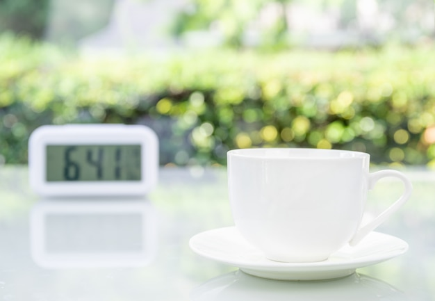 Coffee cup at office with digital clock