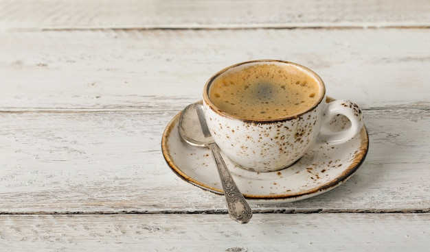 Coffee cup on an old wooden table close up