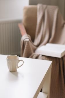 Кофейная чашка на столе рядом с креслом с открытой книгой