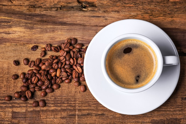 木製のテーブルの上のコーヒーカップ。暗い背景。