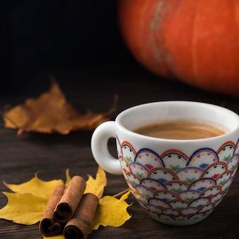 Чашка кофе на осенних листьях над деревянной предпосылкой. осенняя кофейная чашка