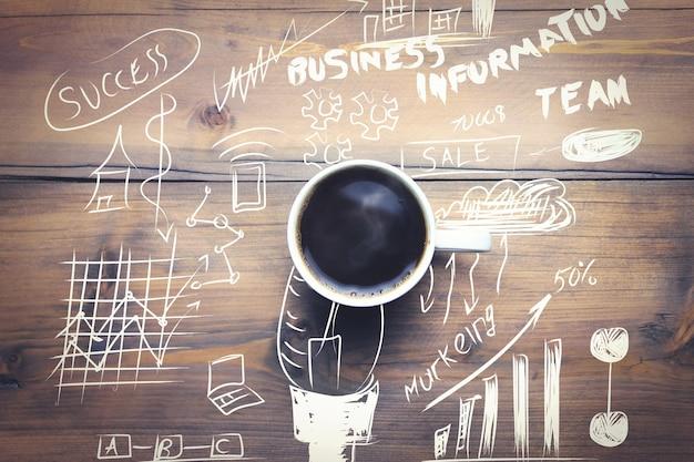 木製のテーブルのグラフ上のコーヒーカップ