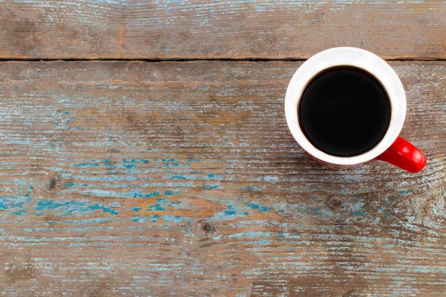 古い木製のテーブルの上のコーヒーカップ。コピースペースの平面図