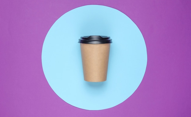 青いパステルサークルと紫の背景にコーヒーカップ。上面図