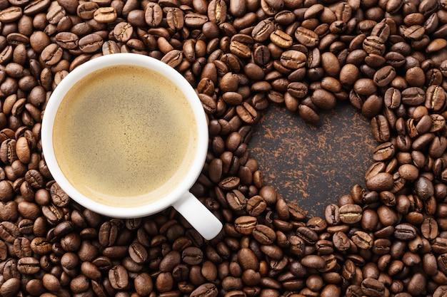 ローストコーヒー豆とハート型のフレームのコーヒーカップ。