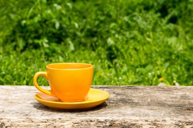 屋外の素朴な木製のテーブルの上のコーヒーカップ