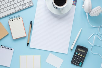 Coffee cup on single line page; spiral notepad; pen; keyboard; headphone against blue background