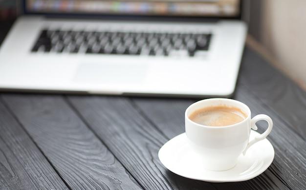 Кофейная чашка на черной таблице на запачканной предпосылке компьтер-книжки для концепции дела.