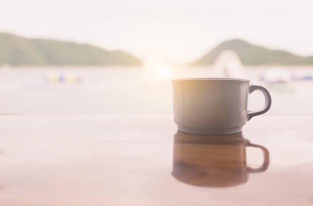 日没のテーブルにコーヒーカップ