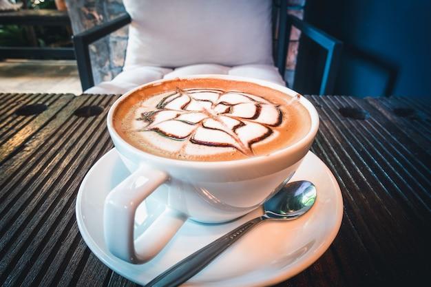 コーヒーカフェショップの木製テーブルの上のコーヒーカップ