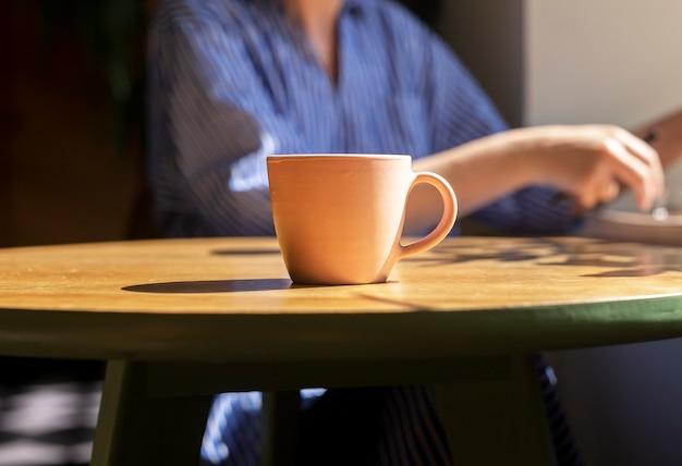 モダンなカフェの木製テーブルの上のコーヒーカップとコーヒーショップの木製の机の上の日光ティーマグ