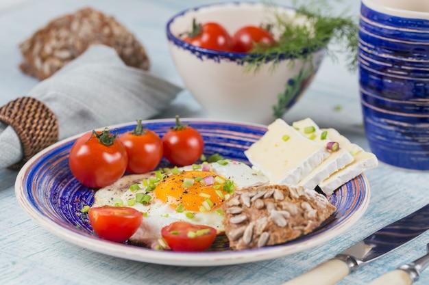 健康的な朝食のためのコーヒーカップ、1つの卵、チーズ、チェリートマト。