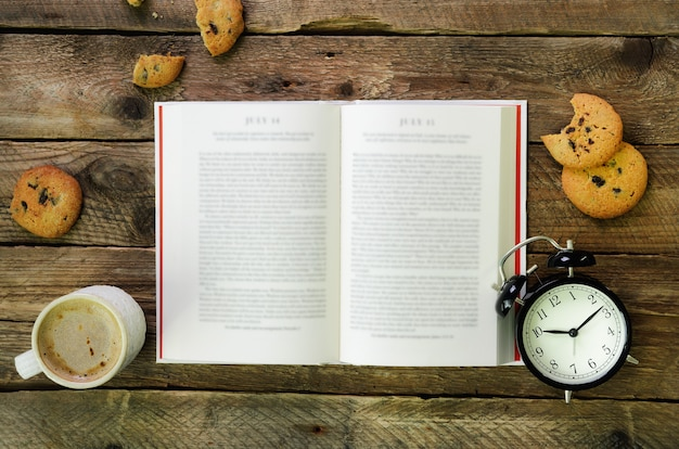 Coffee cup, opened book, alarm clock, cookie on wooden rustic vintage.
