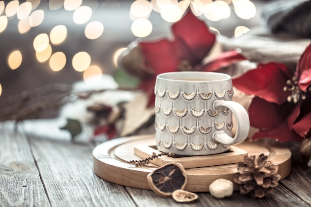 Чашка кофе над боке рождественских огней в доме на деревянном столе с цветами на стене и украшениями. праздничное украшение, волшебное рождество