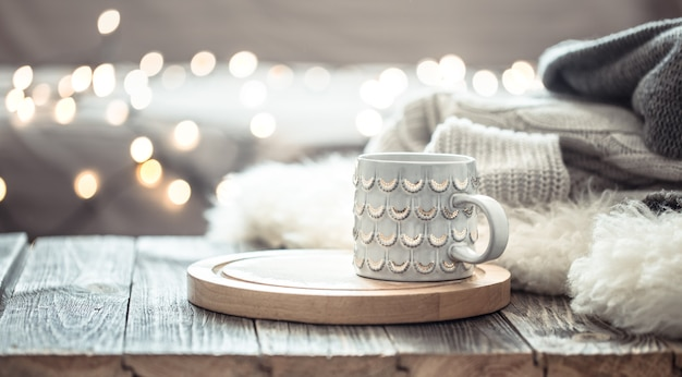 壁にセーターが付いている木製のテーブルの上のクリスマスライトのボケ味の上のコーヒーカップ。休日の装飾、魔法のクリスマス