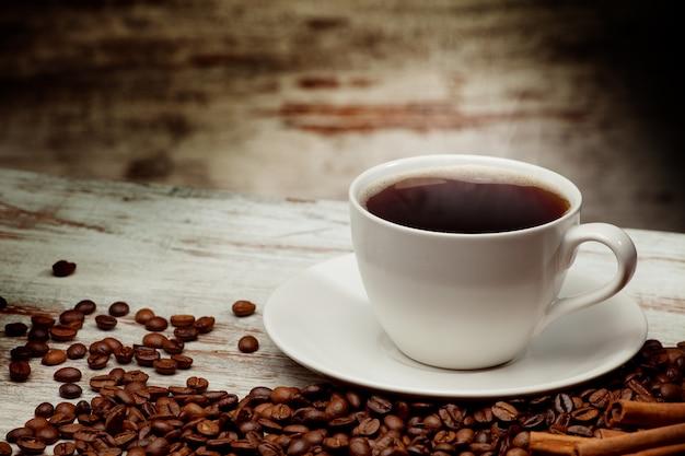 グランジ木製の背景の上のコーヒーカップ