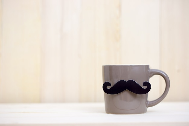 Coffee cup, paper mustache on wooden background with copy space. happy father's day.