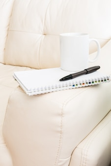 Coffee cup, pen, notebook is on white sofa