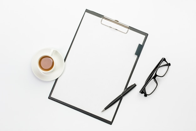 Coffee cup and pen with white paper on clipboard against office desk