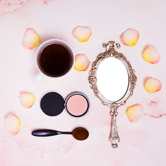 Coffee cup; petals; compact powder; oval brush and compact powder on pink background