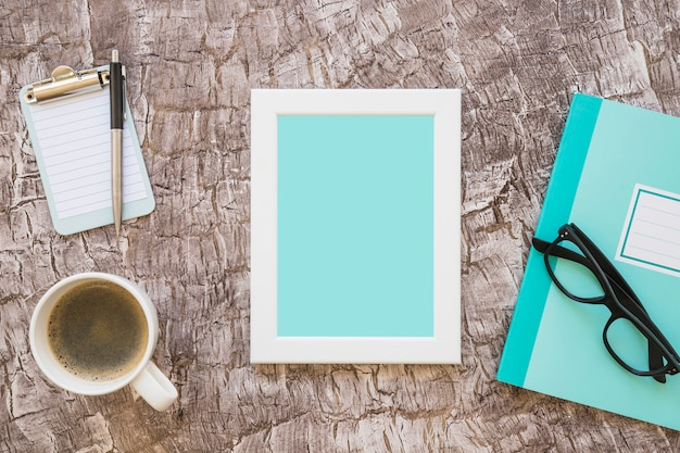 Coffee cup; picture frame; notebook; eyeglasses and miniature clipboard with pen