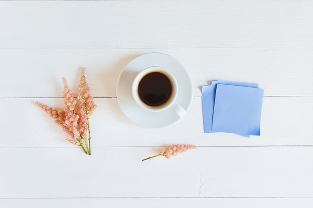 Coffee cup, pink flowers and blue paper stickers on white wooden table. top view, flatlay.