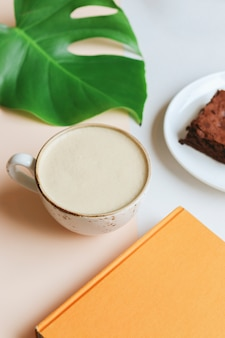 Coffee cup raf with book, monstera and brownie