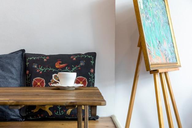Coffee cup and saucer on wooden table in front of cushion and easel