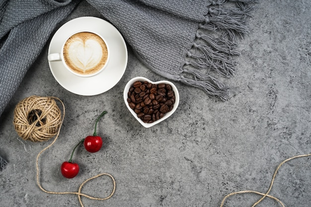 Coffee cup, scarf, cherries and coffee beans