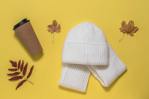 黄色い表面にコーヒーカップ、スカーフ、帽子、紅葉。秋の気分。