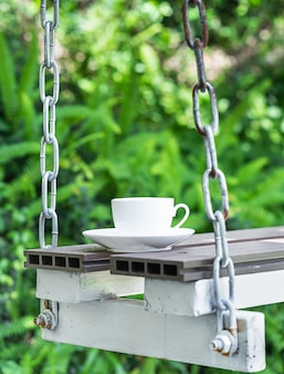 Coffee cup on seat suspended by chains